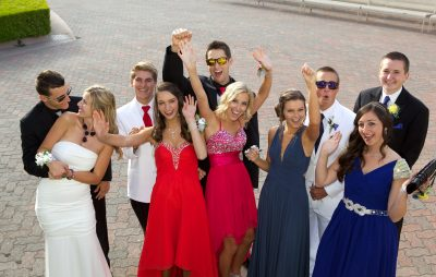 A group of attractive high school students posing for a fun prom photo